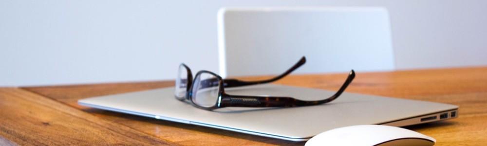 Schreibtisch mit Laptop, Maus und Lesebrille